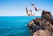 Leinwanddruck Bild - Friends cliff jumping into the ocean