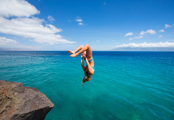 Woman doing backflip into ocean