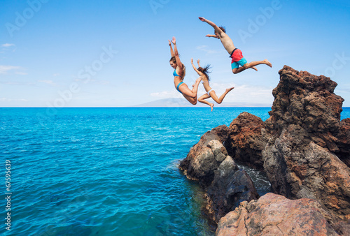 Friends cliff jumping into the ocean - 67595639