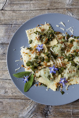 handmade pasta ravioli with borage, flowers and sage on plate