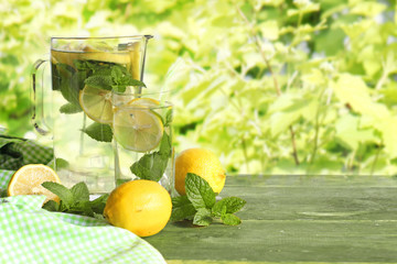 Glass of water with ice, mint and lime in the garden