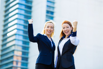 Two ecstatic business woman celebrating success