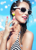 Young attractive woman wearing sunglasses by the pool