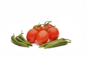 Green chili peppers with red tomatoes on the white background