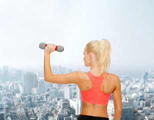 young sporty woman with light dumbbell
