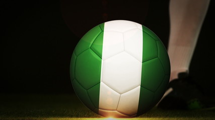 Football player kicking nigeria flag ball