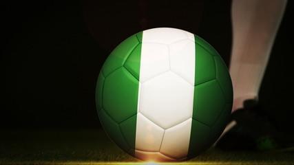 Football player kicking nigeria flag ball