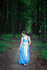 girl in a blue dress walking on the green forest turns around