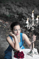 girl sits near table with red roses and keeps candlestick with t