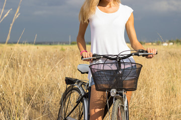 Torso of young woman with bicycle in hay field