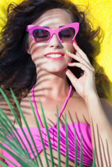 Cheerful woman wearing sunglasses under a palm tree