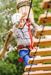 Boy climbing rope-ladder in adrenalin park