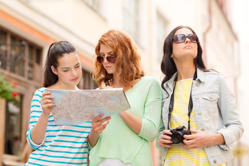 teenage girls with map and camera