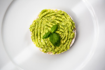 Fresh avocado guacamole on rice bred with basil
