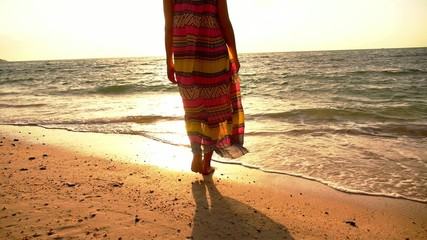 Young Curly Woman Walking on Beach in Long Dress against Sunset.