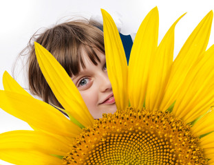 little girl looking out of a hole in sunflower petals