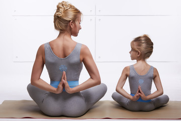 Mother daughter yoga exercise in the same comfortable tracksuits