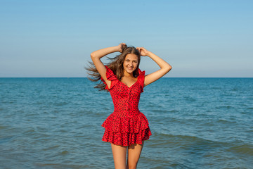 Young woman in red dress on the sea