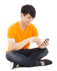 Smiling young student sitting on floor and touching smartphone