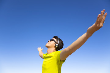 young man enjoying music  with blue sky background