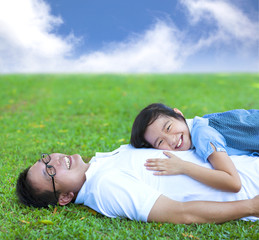 father and daughter lying on a meadow in the park