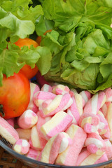 Vegetables salad, tomato and pink marshmallows.