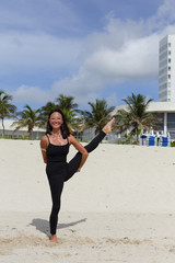 Woman in a balancing yoga pose on the beach