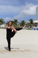 Woman in a yoga balancing pose on the sand