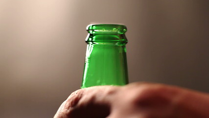 Man's hand opens a beer bottle