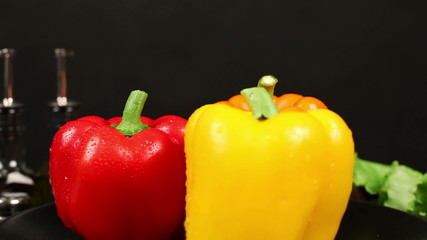 CLOSE UP: Three bell peppers turn in center of frame