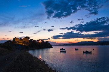 Sunset at Toroni bay with old roman fortress and fishing boats