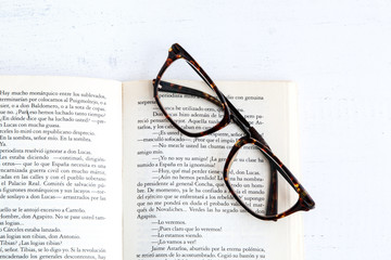Book with glasses on white wooden table