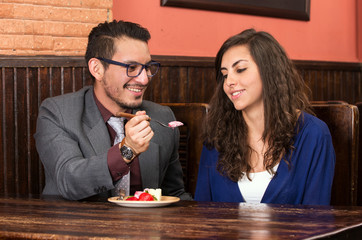 happy couple sharing strawberry dessert in restaurant