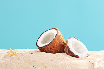 Studio shot of a sliced coconut on a sandy surface