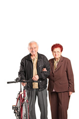 Elderly couple holding hands and pushing a bike