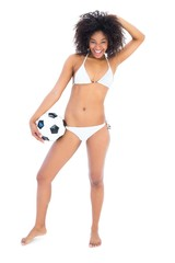 Beautiful fit girl in white bikini holding football smiling at c