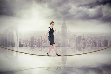 Composite image of businesswoman doing a balancing act on tightr