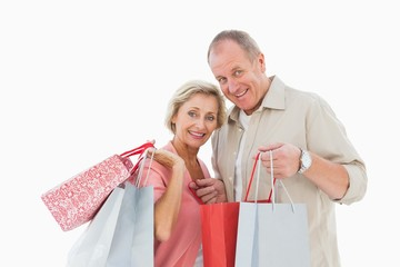 Smiling mature couple holding shopping bags