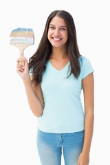Happy young brunette holding paintbrush