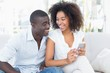 Attractive couple sitting on couch together looking at smartphon
