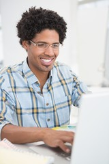 Focused young businessman working on laptop