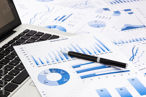 laptop and pen with blue business charts, graphs, statistic and
