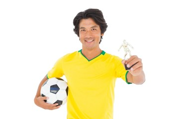 Football player in yellow holding winners trophy