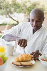 Handsome man in bathrobe having breakfast outside