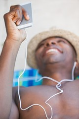 Shirtless man smiling and listening to music on smartphone