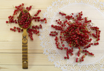 Red currant with spoon on the lace napkin