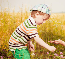 boy taking flower from mother palm
