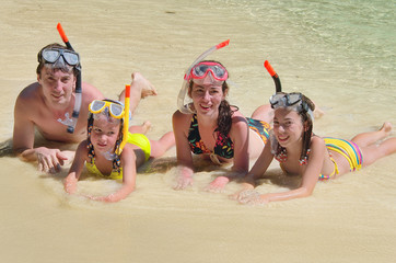 Happy family in snorkels on tropical beach having fun