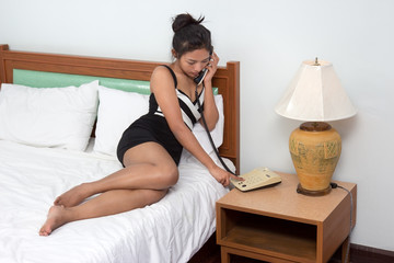 woman calling from the phone on the bed