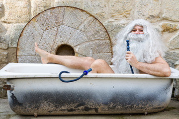man bathes in an outdoor bathtub